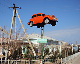A bright orange car attracts visitors to a restaurant in the village of Jangikishlak